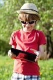 Joyful boy plays in the Tablet PC Stock Photo