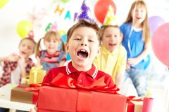 Joyful boy. With present looking at camera with his friends on background Stock Photo