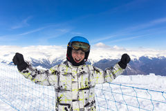 Joyful boy in protective ski helmet. On scenery mountain top view background Stock Image