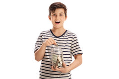 Joyful boy putting a coin into a jar Stock Images