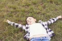 Joyful boy relaxing on green grass royalty free stock images