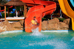 Joyful boy rides in the water park. Summer day Royalty Free Stock Photos