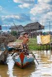 Joyful Boy Rowing Boat on Tonle Sap Lake, Cambodia Royalty Free Stock Photo
