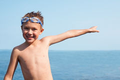 Joyful boy shows his hand towards the sea. Royalty Free Stock Image
