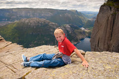 The joyful boy sits on the edge of the rock in Norway, Pulpit Ro. The bright clothes contrast with the gray rocks of Norway and magic-blue prospect opening from Royalty Free Stock Image