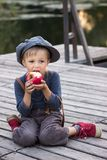 Joyful boy sitting with apple. On the river bank Stock Photo