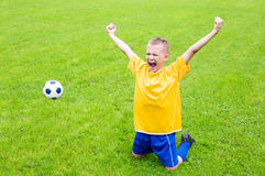 Joyful boy soccer player. After goal scored. Natural grass Stock Photo