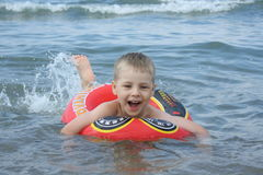 The joyfull boy is swiming in the sea. With a rubber ring Royalty Free Stock Photos
