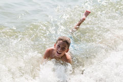 Joyful boy swimming. Happy young boy playing in the waves at a beach Stock Image
