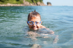 Joyful boy swims in the sea. With glasses for swimming Royalty Free Stock Images