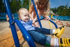 Joyful boy on swing. Joyful boy swinging on blue swing in amusement park, pretty girl shakes her son on blue swing in park, concept of happy family Stock Photography