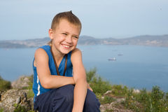 Joyful boy on top of a mountain. In the background of the sea coast Royalty Free Stock Photos
