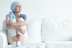 Joyful breast cancer survivor. Holding her knees while relaxing on a couch royalty free stock photos