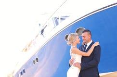 Joyful bridal couple embracing near boats Stock Image
