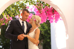 Joyful bridal couple embracing near colorful flowers Stock Photos