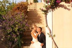 Joyful bridal couple embracing near colorful flowers Royalty Free Stock Image