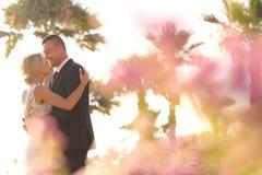 Joyful bridal couple embracing near colorful flowers Royalty Free Stock Images