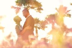 Joyful bridal couple embracing near colorful flowers Stock Photo
