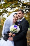 Joyful bride and groom in autumn park Stock Photography