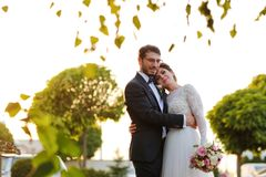 Joyful bride and groom with bouquet embracing Royalty Free Stock Photo