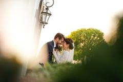 Joyful bride and groom with bouquet embracing Stock Photos