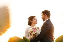 Joyful bride and groom with bouquet embracing Royalty Free Stock Photography