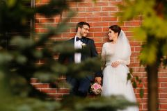 Joyful bride and groom with bouquet embracing Royalty Free Stock Images