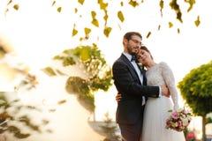Joyful bride and groom with bouquet embracing Stock Image