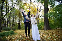 Joyful bride and groom throw the yellow leaves Stock Photos