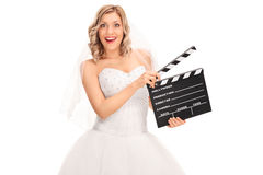 Joyful bride holding a movie clapperboard. Joyful young bride in a white wedding dress holding a movie clapperboard isolated on white background Royalty Free Stock Image