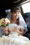 Joyful bride into limo Stock Image
