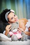 Joyful bride with teddy bear on white bed Royalty Free Stock Image