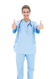 Joyful brown haired nurse in blue scrubs giving thumbs up Stock Photography