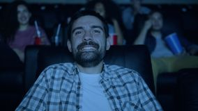 Joyful brunet watching funny movie in cinema laughing having fun in dark room. Joyful brunet is watching funny movie in cinema laughing having fun sitting in stock footage