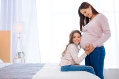 Joyful brunette girl listening her pregnant moms tummy stock photos
