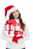 Joyful brunette in santa hat and red gloves holding pile of gifts Royalty Free Stock Image