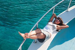 Joyful brunette woman laying on yacht deck Royalty Free Stock Photo