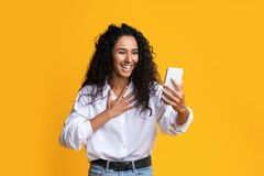 Free Joyful Brunette Woman Making Video Call With Smartphone Over Yellow Studio Background Stock Photography - 197475622