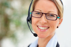 Joyful business woman speaking using headset Stock Photography