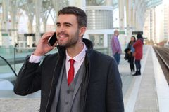 Joyful businessman calling by phone from train station Stock Photography