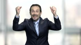 Joyful businessman clenching his fists in excitement. Ecstatic middle aged entrepreneur celebrating victory with hands gesture. Successful deal concept stock video footage