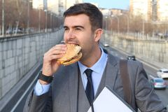 Joyful businessman devouring a hamburger Stock Photography