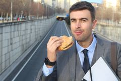 Joyful businessman devouring a hamburger Royalty Free Stock Images