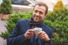 Joyful businessman enjoying hot beverage. Happy man is drinking coffee and relaxing. He is sitting outdoors and laughing Royalty Free Stock Photos