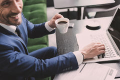 Joyful businessman enjoying hot beverage during online work. Top view of excited man in suit drinking coffee in cafe. He is using modern computer and laughing Royalty Free Stock Photos