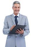 Joyful businessman holding clipboard and taking notes Royalty Free Stock Photo