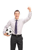 Joyful businessman holding a football and cheering Stock Photography