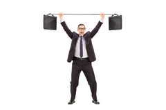 Joyful businessman lifting two briefcases on a bar Royalty Free Stock Photography