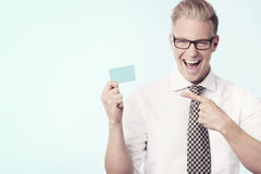 Joyful businessman pointing finger at empty card. Stock Images