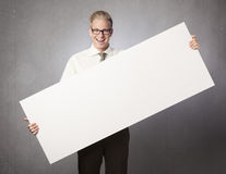 Joyful businessman presenting white blank billboard. Stock Image